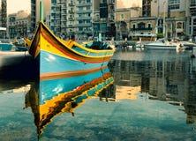 Maltese boat in St. Julian's Bay, Malta. Colorful fishermen's boat reflected in water in St. Julian's Bay, Malta Stock Photos