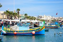 Maltese boats moored in Marsaxlokk harbour. Traditional Maltese Dghajsa fishing boats in the harbour with waterfront buildings and market stalls to the rear Stock Photography