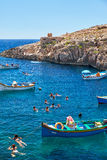 Maltese boats and swimming people in water of Wied Zurrieq Fjord. Wied Zurrieq Fjord, MALTA - JULY 24, 2015: Maltese boats and swimming people in water near Blue Royalty Free Stock Photo