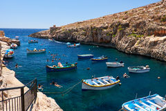 Maltese boats and swimming people in water of Wied Zurrieq Fjord. Wied Zurrieq Fjord, MALTA - JULY 24, 2015: Maltese boats and swimming people in water near Blue Stock Images