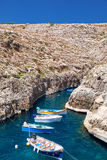 Maltese boats on transparent green water of Wied Zurrieq Fjord o. N south end of Malta island Stock Photo