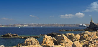 Malta, Seaside view. Rocky shore in the northwest Malta and panoramic view of Gozo island in the background, Cirkewwa, Malta Royalty Free Stock Image