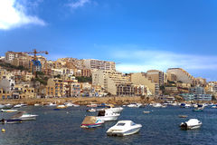 Malta, Coastline view. Fishing boats, motor boats and yachts moored in the St Pauls Bay and panorama of Xemxija in the background Stock Images