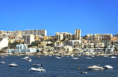 Malta, Coastline view. Vessels moored in the St Pauls Bay and panorama of Xemxija in the background Stock Images