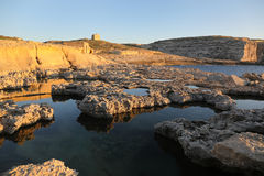 Maltese coastline on sunny day. Maltese coastline with cliffs and old watch tower Royalty Free Stock Images