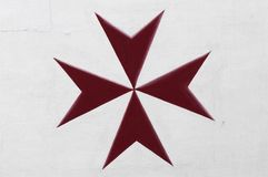 Maltese Cross. Red Maltese Cross painted on white wall Stock Image