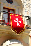Maltese cross banner. Hangs from a balcony Royalty Free Stock Photography