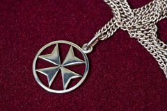 Maltese cross pendant. A Maltese cross silver pendant on velvet background Royalty Free Stock Images
