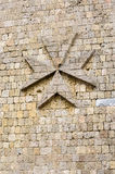 Maltese Cross. In relief on the casstle's wall Stock Photo