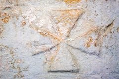 Maltese cross on stone wall. Relief of Maltese cross on stone wall of ancient tomb Stock Photos