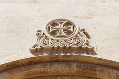 Maltese cross on the wall. Of the building bas-relief Stock Photos