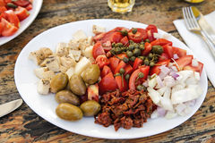 Maltese cuisine. Traditional Maltese plates with different ingredients and with Gbejna, a small round cheese made in Gozo, Malta Royalty Free Stock Photo