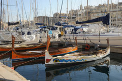 Maltese Dghajsa. Boats alongside the yachts of millionaire's. Grand Harbour, in the Mediterranean port of Malta. March 2013 Royalty Free Stock Images