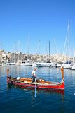 Maltese Dghajsa water taxi, Vittoriosa. Man steering a traditional Maltese Dghajsa water taxi in the harbour with views towards Senglea waterfront, Vittoriosa Stock Images