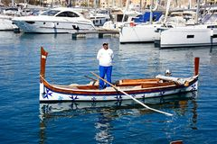 Maltese Dghajsa water taxi, Vittoriosa. Oarsman standing in a traditional Maltese Dghajsa water taxi in the harbour with views towards Senglea waterfront Stock Images
