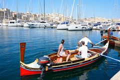 Maltese Dghajsa water taxi, Vittoriosa. Passengers on board a traditional Maltese Dghajsa water taxi in the harbour with views towards Senglea waterfront Royalty Free Stock Photography