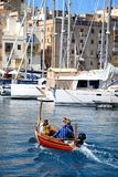 Maltese Dghajsa water taxi, Vittoriosa. Passengers on board a traditional Maltese Dghajsa water taxi in the harbour with views towards Senglea waterfront Stock Photos