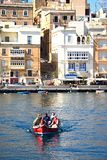 Maltese Dghajsa water taxi, Vittoriosa. Passengers on board a traditional Maltese Dghajsa water taxi in the harbour with views towards Senglea waterfront Royalty Free Stock Image