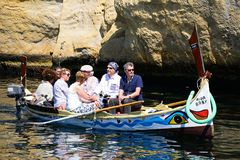 Maltese Dghajsa water taxi, Vittoriosa. Passengers on board a traditional Maltese Dghajsa water taxi in an inlet alongside Fort San Angelo, Vittoriosa, Malta Royalty Free Stock Photography