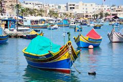 Maltese Dghajsas in the harbour, Marsaxlokk. Traditional Maltese Dghajsa fishing boats in the harbour with waterfront buildings to the rear, Marsaxlokk, Malta Stock Images