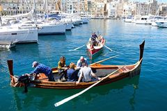 Maltese Dghajsas in the marina, Vittoriosa. Passengers on board traditional Maltese Dghajsa water taxis in the harbour with views towards Senglea waterfront Stock Photo