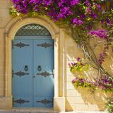 Maltese door decorated with flowers. Building with traditional maltese door decorated with fresh flowers in Mdina Stock Photo