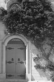 Maltese door decorated with flowers. Building with traditional maltese door decorated with fresh flowers in Mdina. Black and white picture Stock Images