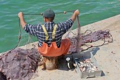 Maltese fisherman examining his nets Royalty Free Stock Image