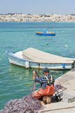 Maltese fisherman repairing his nets Stock Photography