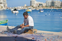 Maltese fisherman repairing his nets Stock Photos