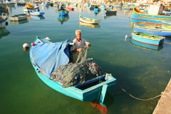 Fisherman in boat tending his nets Stock Photos