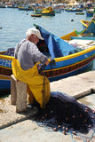 An old fisherman at work Malta. A maltese fisherman working his nets against a backdrop of traditional Maltese Luzzu fishing boats, Marsaxlokk Harbor Royalty Free Stock Image