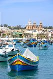 Maltese fishing boats in Marsaxlokk harbour. Traditional Maltese Dghajsa fishing boats in the harbour with the parish church of Our Lady of Pompei to the rear Royalty Free Stock Photo