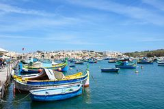 Maltese fishing boats moored in Marsaxlokk harbour. Traditional Maltese Dghajsa fishing boats in the harbour with waterfront buildings to the rear, Marsaxlokk Royalty Free Stock Images