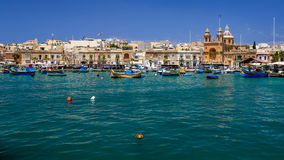 Maltese fishing village with boats and church. Marsaxlokk, Malta fishing village with boats on clear blue water Royalty Free Stock Images