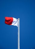 Maltese flag against a blue sky. The Maltese flag atop a flagpole in Castille Square against a blue sky, Valletta, Malta, Europe Royalty Free Stock Photo