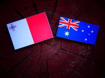 Maltese flag with Australian flag on a tree stump isolated. Maltese flag with Australian flag on a tree stump Royalty Free Stock Images