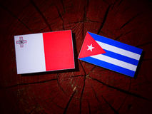 Maltese flag with Cuban flag on a tree stump isolated Stock Photo