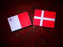 Maltese flag with Danish flag on a tree stump isolated Royalty Free Stock Photo
