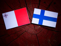 Maltese flag with Finnish flag on a tree stump isolated Stock Photography