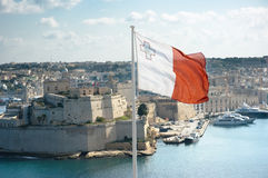 Maltese Flag Is Flying From Upper Barrakka Gardens. The maltese flag is flying from upper Barrakka gardens in Valletta and on the background the fortifications Royalty Free Stock Photography