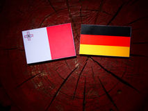 Maltese flag with German flag on a tree stump. Maltese flag with German flag on a tree stump Royalty Free Stock Images