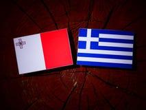 Maltese flag with Greek flag on a tree stump isolated. Maltese flag with Greek flag on a tree stump Stock Photo
