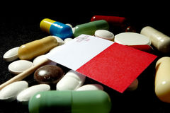 Maltese flag with lot of medical pills isolated on black background Stock Photos
