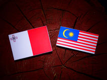 Maltese flag with Malaysian flag on a tree stump isolated Stock Image