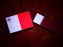 Maltese flag with Qatari flag on a tree stump isolated Stock Photo