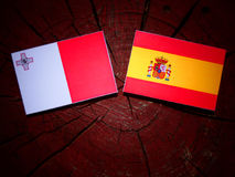 Maltese flag with Spanish flag on a tree stump. Maltese flag with Spanish flag on a tree stump Royalty Free Stock Images