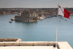 Maltese flag and St. Angelo. Fort St. Angelo, now being renovated to its former glory stands at the centre of Grand harbour, Malta Stock Photos