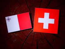 Maltese flag with Swiss flag on a tree stump isolated. Maltese flag with Swiss flag on a tree stump Royalty Free Stock Photography
