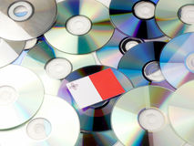Maltese flag on top of CD and DVD pile isolated on white. Maltese flag on top of CD and DVD pile isolated Royalty Free Stock Photo